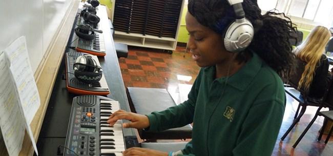 Muskegon Catholic Central music & arts programs - student at piano keyboard
